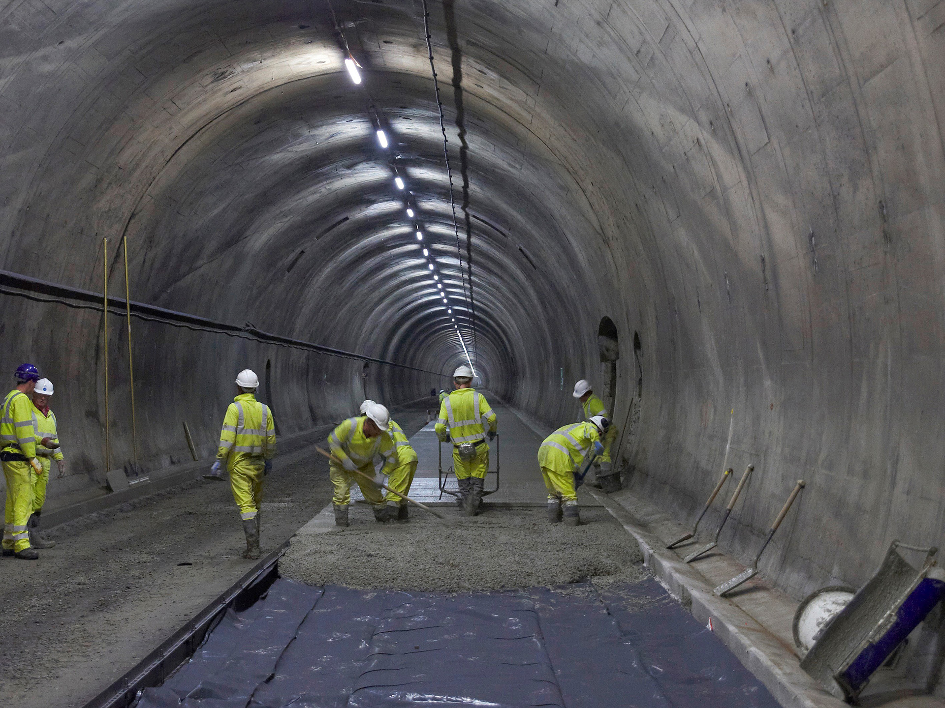 flooring contractors working in a tunnel hand laying concrete flooring