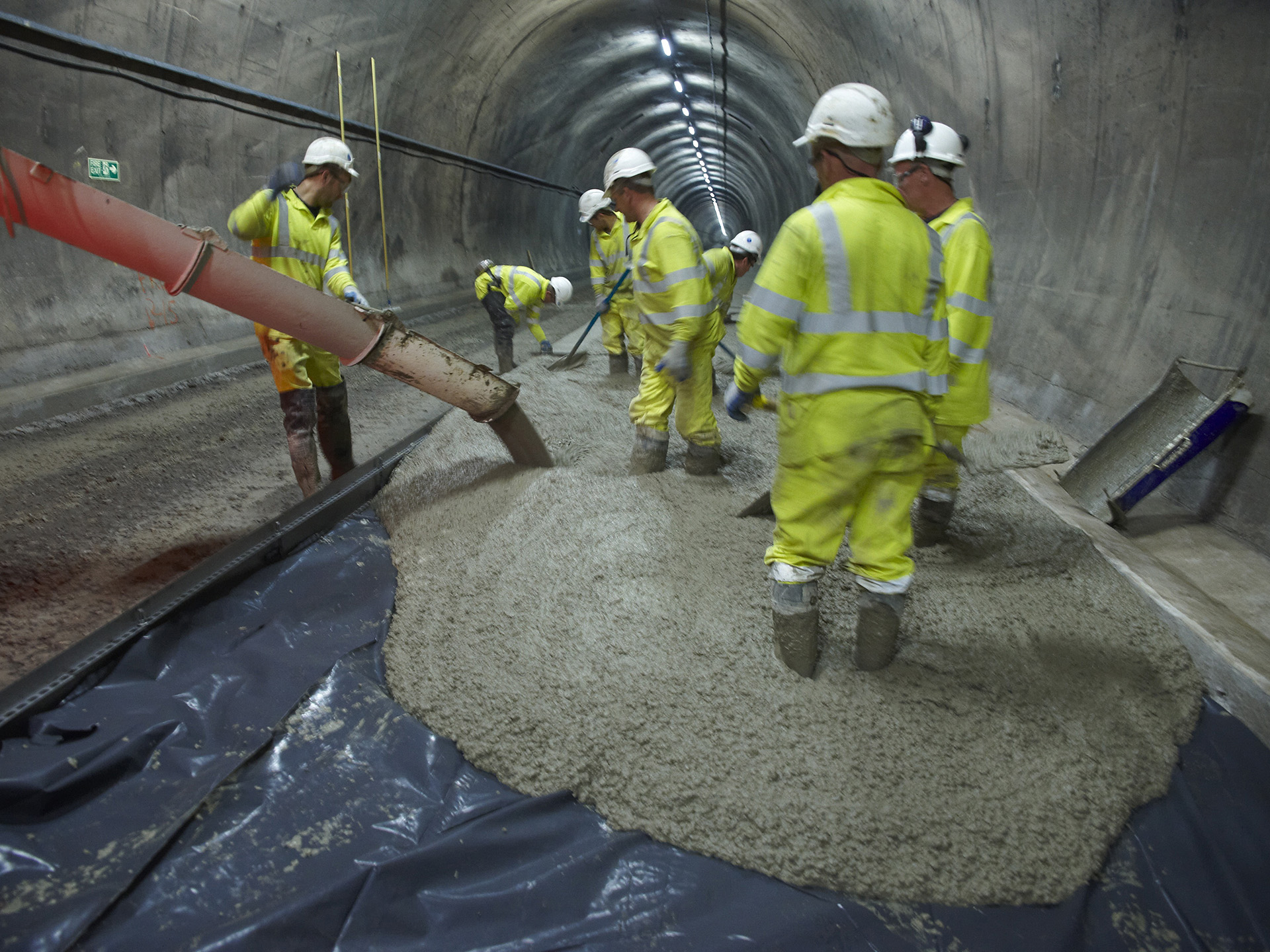 concrete flooring contractors at work in a tunnel