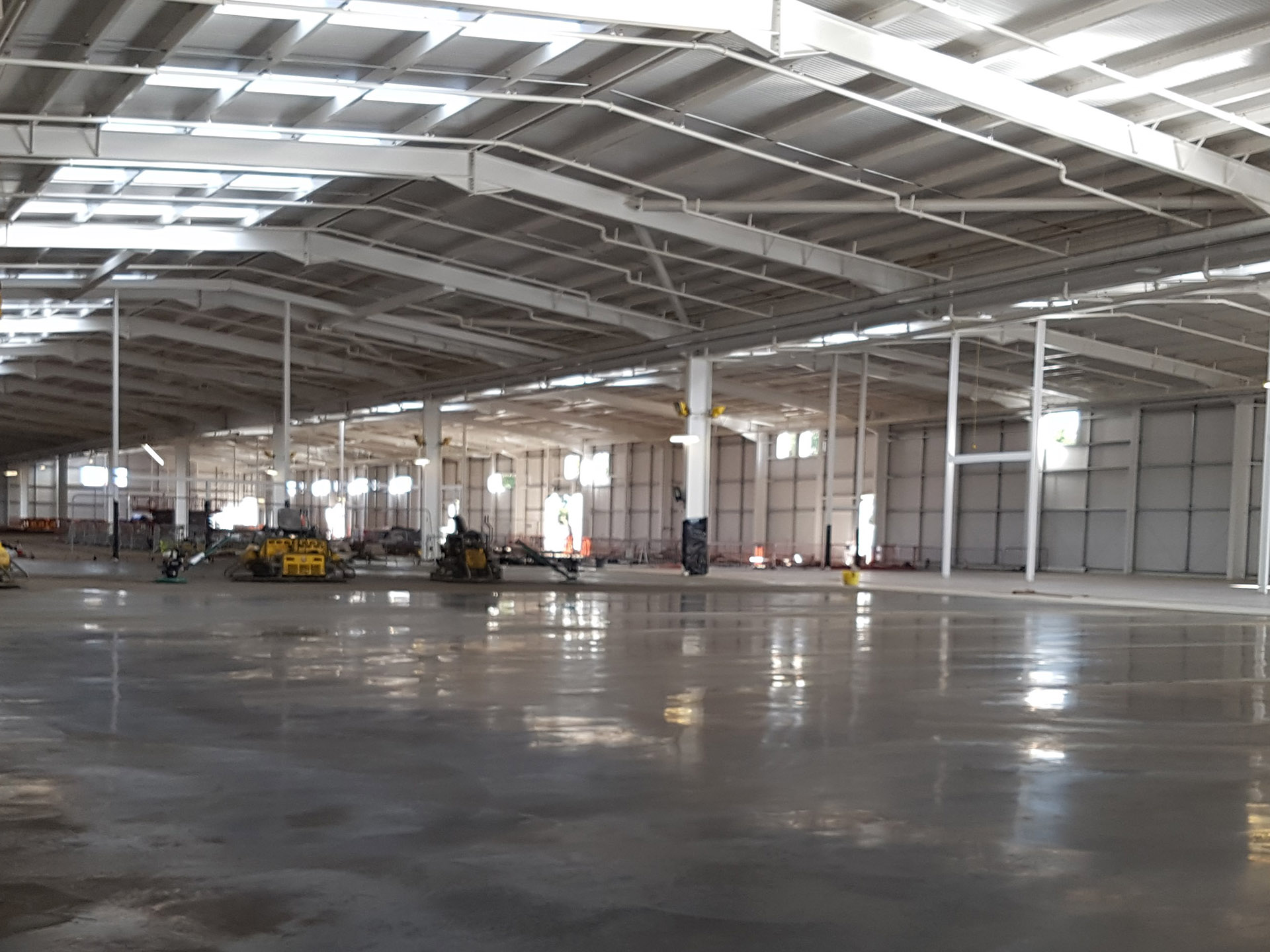 contractors laying concrete floor in a warehouse